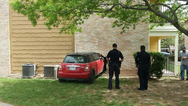MINI in wall, cops look on